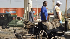 A military vehicle and people pass site of an explosion at a police station in Kano