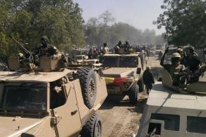Chadian soldiers drive through the streets of Gambaru