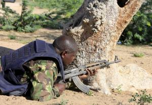 A Kenya Defense Force soldier takes cover near the perimeter wall where attackers are holding up at a campus in Garissa