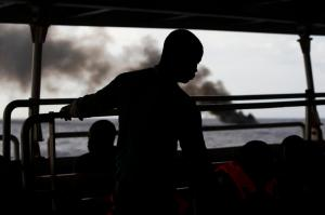 Migrants rest under the heli-pad of the NGO Migrant Offshore Aid Station (MOAS) ship Phoenix as their rubber dinghy is burnt and sunk after their group of 104 sub-Saharan Africans was rescued some 25 miles off the Libyan coast in this October 4, 2014 file photo. As many as 900 people may have died in Sunday's disaster off the coast of Libya. That would be the highest death toll in recent times among migrants, who are trafficked in the tens of thousands in rickety vessels across the Mediterranean. The mass deaths have caused shock in Europe, where a decision to scale back naval operations last year seems to have increased the risks for migrants without reducing their numbers. The European Union has proposed doubling the size of its Mediterranean search and rescue operations in response to the crisis.  REUTERS/Darrin Zammit Lupi/Files   MALTA OUT. NO COMMERCIAL OR EDITORIAL SALES IN MALTA PICTURE 08 OF 28 FOR WIDER IMAGE STORY 'ISLE LANDERS' SEARCH 'DARRIN ISLE' FOR ALL IMAGES