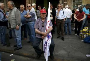 A Greek pensioner holds a flag during a demonstration for better healthcare in Athens