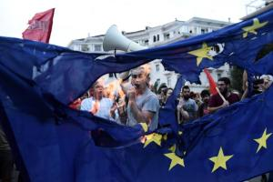 Members of left wing parties burn a European Union flag during a protest in the northern Greek port city of Thessaloniki, Sunday, June 28, 2015.  Greek Prime Minister Alexis Tsipras says the Bank of Greece has recommended that banks remain closed and restrictions be imposed on transactions, after the European Central Bank didn't increase the amount of emergency liquidity the lenders can access from the central bank. (AP Photo/Giannis Papanikos)